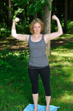 Young woman flexing muscles in park Stock Photography