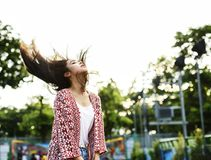 Young woman flinging her hair at an amusement park Stock Photo