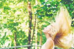 Young woman flipping her hair outside on a beautiful day. Young woman flipping her hair outside on a beautiful summer day Royalty Free Stock Images