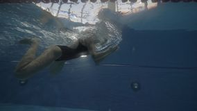 Young woman floating breaststroke in swimming waterpool underwater view. Young woman swimming breaststroke in waterpool underwater view. Close up training woman stock video