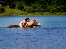 Young woman floating on the lake in the back of a horse. Stock Photo