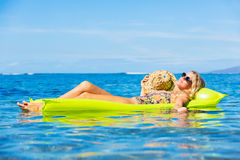 Young woman floating on raft Stock Photography