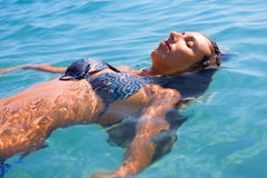 Young woman floating in the sea royalty free stock photography