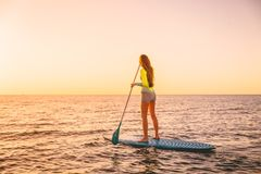 Young woman floating at stand up paddle board with warm sunset colors. Sporty woman floating at stand up paddle board with colorful sunset royalty free stock photography