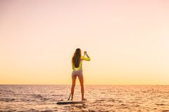 Young woman floating at stand up paddle board with warm sunset colors. Sporty woman floating at stand up paddle board with colorful sunset stock photos