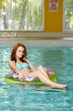 Young woman floating in swimming pool royalty free stock image