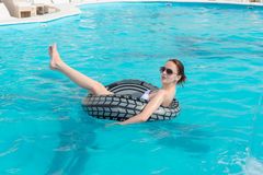 Young woman floating in a turquoise blue pool. Relaxing in a rubber tube with her leg raised in the air as she enjoys her summer vacation Stock Photography