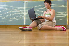 Young woman on floor using laptop computer, ground view. Young women on floor using laptop computer, ground view Stock Images