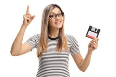 Young woman with a floppy disk holding her index finger up Stock Photo