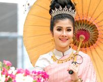 Young woman on a floral float in flower festival parade. Chiang Mai, Thailand-February 3, 2018: Young woman in traditional costumes, sitting in the elaborate Royalty Free Stock Image