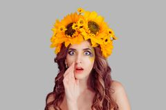 Woman with floral headband holding hand near mouth and telling secret stock image