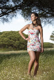 Young woman in a floral tight and short dress Stock Photography