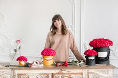 Young woman florist arranging plants in flower shop. People, business, sale and floristry concept. Bouquet of red roses. Smiling lovely young woman florist royalty free stock photo