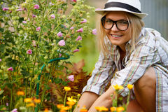 Young woman florist working in garden and looking at camera Royalty Free Stock Photos