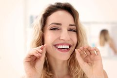 Young woman flossing her teeth. Indoors royalty free stock images