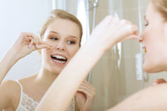 A young woman flossing her teeth Royalty Free Stock Photos