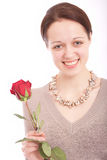 The young woman with a flower. The smiling girl in a necklace and with a rose in a hand royalty free stock image
