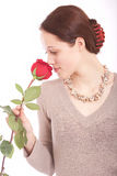 The young woman with a flower. The girl in a necklace enjoys a rose smell royalty free stock image