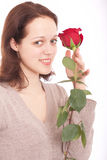 The young woman with a flower. Portrait of the smiling girl with a rose in a hand royalty free stock image