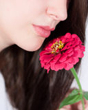 Young woman with a flower. Woman smelling the fragrance of a flower Royalty Free Stock Photo