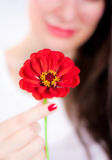Young woman with a flower. Young woman in the background holding a beautiful red flower Stock Photo