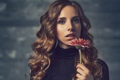 Young woman portrait. Young woman with flower and curly hair portrait in soft colors Royalty Free Stock Images