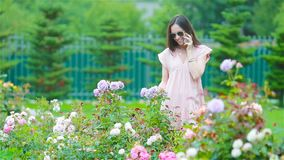 Young girl in a flower garden among beautiful roses. Smell of roses stock footage
