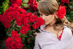 Young woman in flower garden smelling red roses. Romantic young woman in flower garden smelling red roses Royalty Free Stock Photos