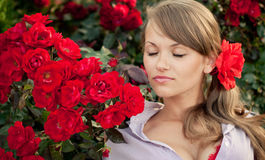 Young woman in flower garden smelling red roses. Romantic young woman in flower garden smelling red roses Stock Photo