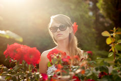 Young woman in flower garden smelling red roses #3 Royalty Free Stock Photography