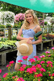 Young Woman in Flower Nursery. Young woman with hat and shovel in flower nursery Royalty Free Stock Photography