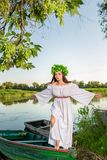 Young woman with flower wreath on her head, relaxing on boat on river at sunset. Concept of female beauty, rest in the