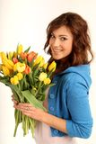 Young woman with flowers. Young brunette woman with yellow and red flowers royalty free stock photos