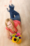 Young Woman with Flowers. Beautiful young woman with a bouquet of colorful flowers laying on the floor. Shot from above, hard-wood floor as background Royalty Free Stock Photo
