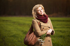 Sad young woman walking in autumn field. Young woman with a flowers in autumn field Royalty Free Stock Photography