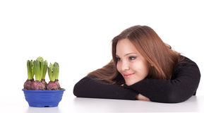Young woman with flowers in flowerpot Royalty Free Stock Photo