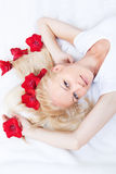 Young woman with flowers in hair on the white bed Stock Image