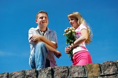 Young woman with flowers and her boyfriend Stock Images