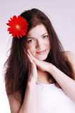 Young woman with flowers in her hair. Girl with red herbera in hair Stock Photo