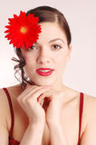 Young woman with flowers in her hair. Young pretty girl with red herbera in her hair Royalty Free Stock Images