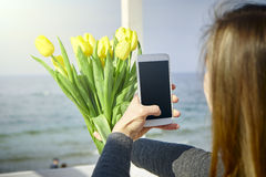 Young woman with flowers making selfie stock photo