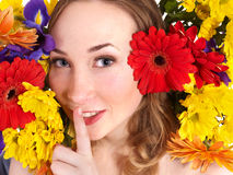 Young woman in flowers making silence gesture. Royalty Free Stock Photos