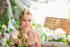 Young woman among the flowers. Outdoor portrait of beautiful blonde young woman posing next to flowers Royalty Free Stock Photos
