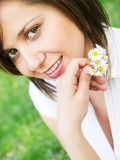 Young woman with flowers. Young woman outdoors, looking at camera Royalty Free Stock Image