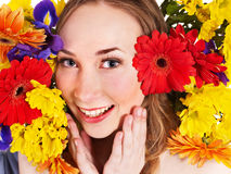 Young woman in flowers touching face. Stock Photo