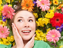 Young woman in flowers touching face. Stock Photos