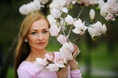Young woman at the flowers of tree branches in spring. Stock Photo
