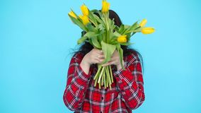 Young woman with flowers tulips in hands on a blue background. Happy Young woman with flowers tulips in hands on a blue background stock video