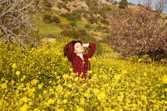 Young woman and flowers. Young pretty woman in yellow daisy flowers field Royalty Free Stock Photos