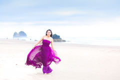 Young woman in flowing magenta dress standing on beach Stock Photos